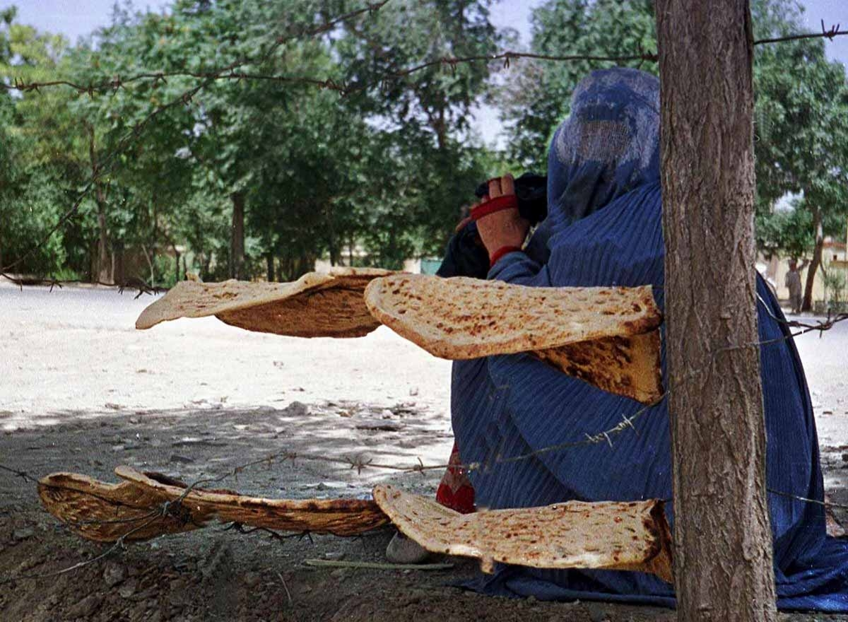 An Afghan woman sits by the bread she received from a UN subsidized backery in Kabul 13 June 2001