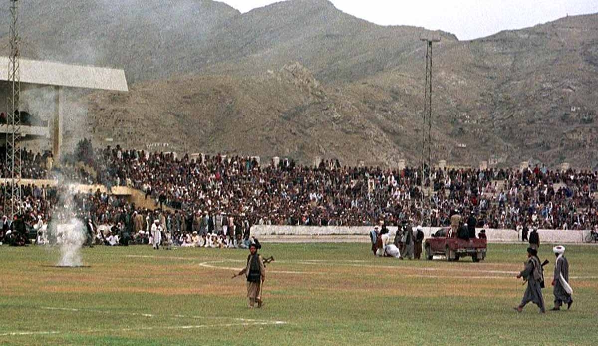 Taliban fighters and Kabul residents watch as surgeons cut off a thief's hand at the national stadium in Kabul, under Taliban rule. August, 1998.