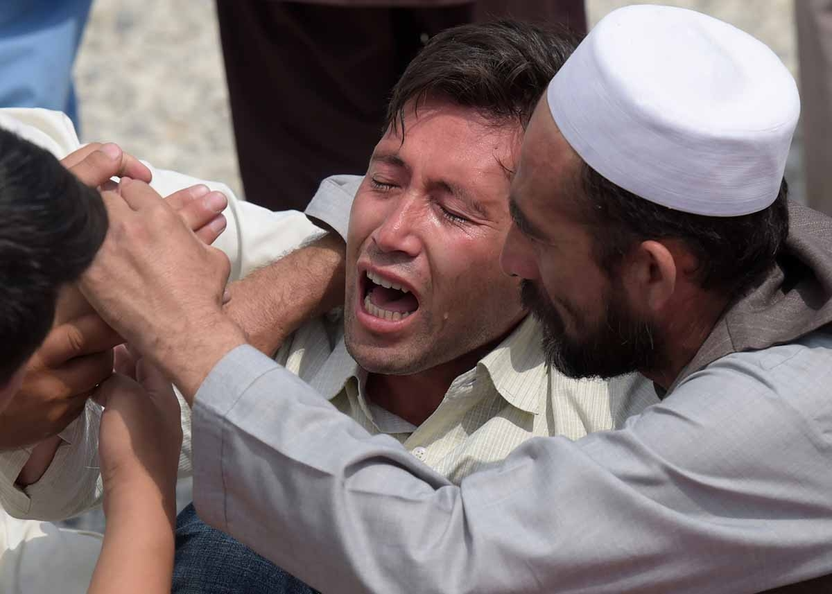 A relative (C) is comforted as he weeps alongside unseen shoes and other belongings of those who were killed in the twin suicide attack, at a mosque in Kabul on July 24, 2016