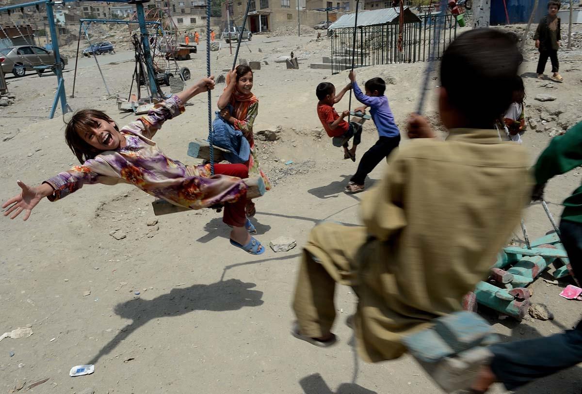 Niños afganos juegan en columpios en Kabul, en 2013 (AFP / Shah Marai)