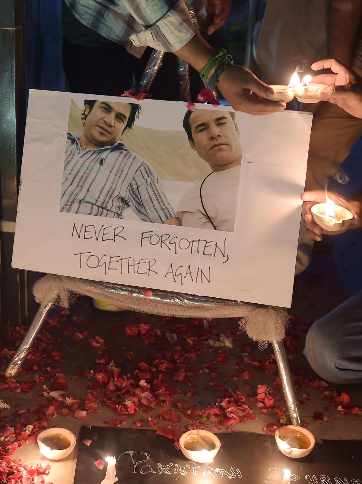 Periodistas prenden velas junto a las fotografías de Shah Marai y su amigo y colega de AFP Sardar Ahmad (izquierda), quien murió en un atentado en Kabul en 2014