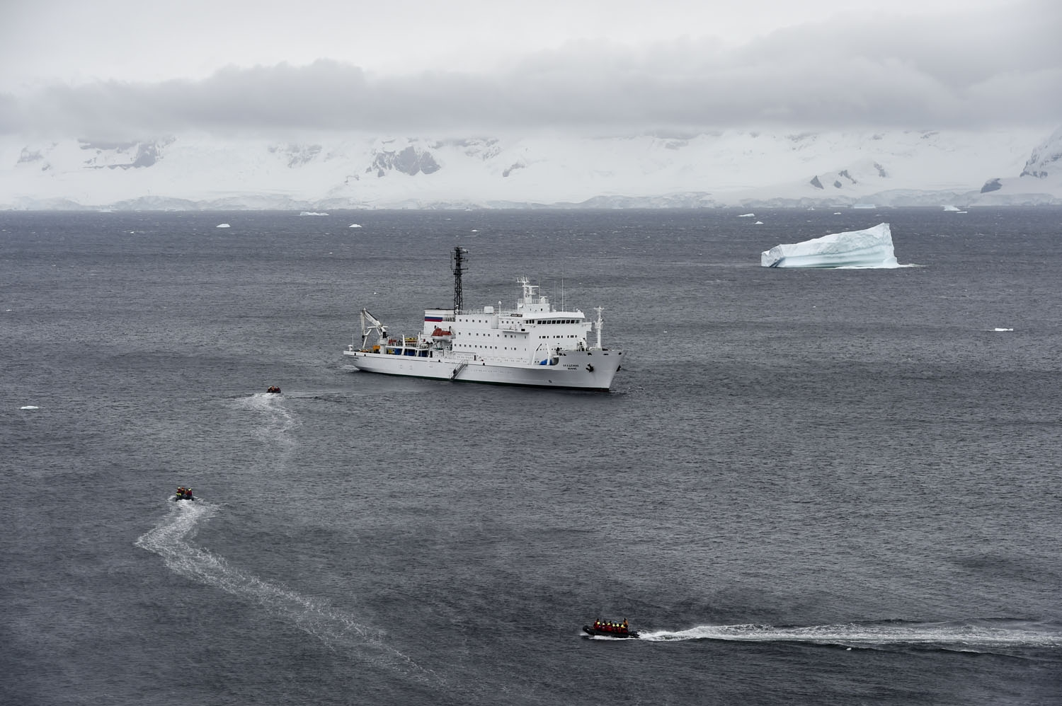 Tourist aboard zodiacs make their way to the oceanographic acoustic research vessel Akademik Ioffe in the western Antarctic peninsula on March 05, 2016