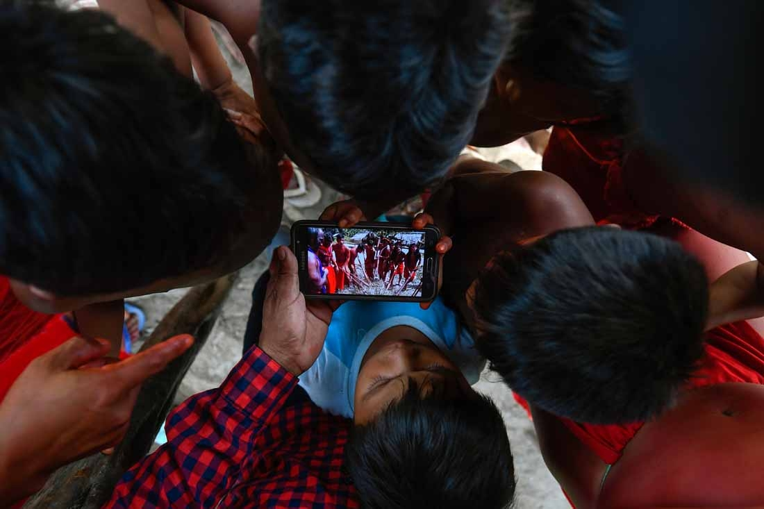 Waiapi children watch a video of a traditional Waiapi dance in a mobile phone at the Manilha village at the indigenous reserve Waiapi in Amapa state in Brazil on October 12, 2017.  The Waiapi are one of the most traditional tribes in Brazil's Amazon, but