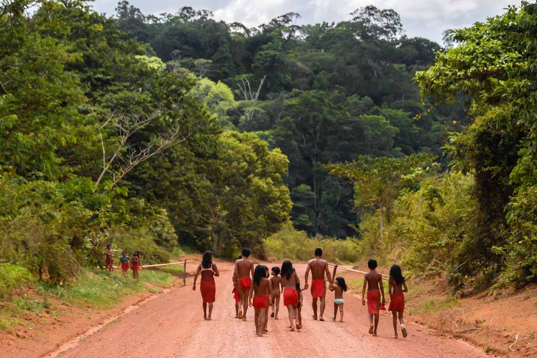 Brazilian Waiapi walk on the road of the Waiapi indigenous reserve, at Pinoty village in Amapa state in Brazil on October 12, 2017.  The Waiapi are one of the most traditional tribes in Brazil's Amazon, but modern life is getting closer – and the forest d
