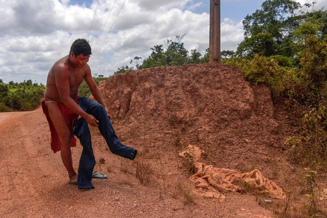 Kamon Waiapi puts on pants right before arriving at the city of Pedra Branca do Amapari in Amapa state in Brazil on October 15, 2017.  The Waiapi are one of the most traditional tribes in Brazil's Amazon, but modern life is getting closer – and the forest