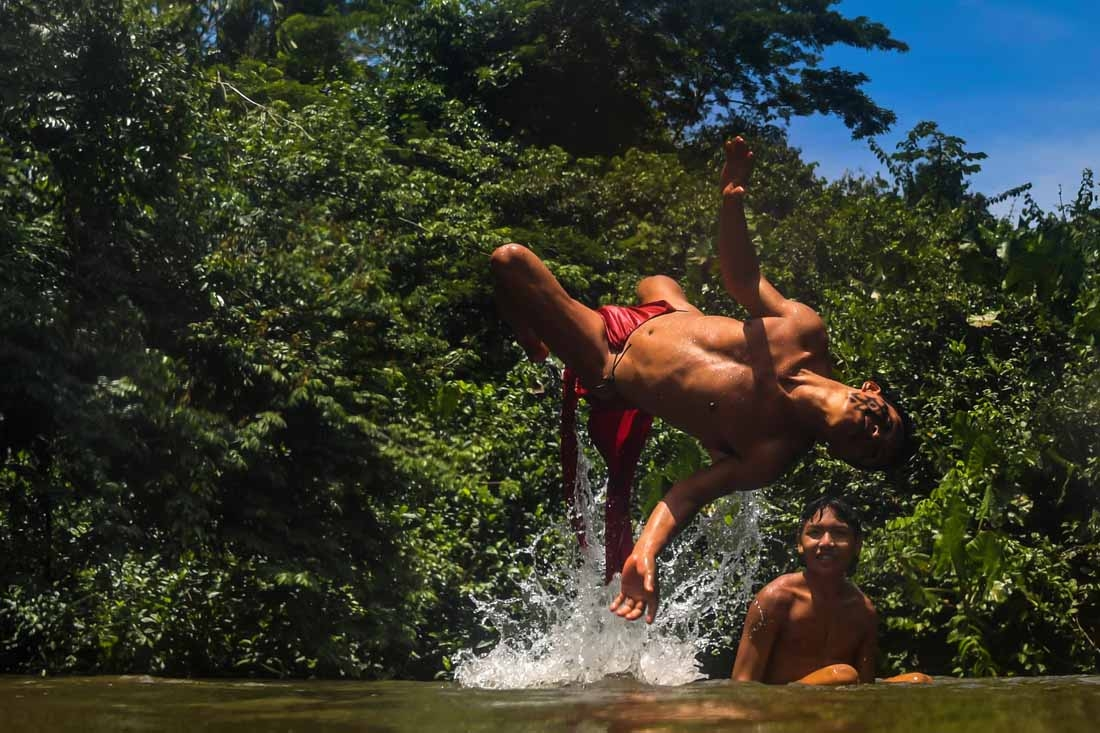 Waiapi men enjoy the Feliz river in the Waiapi indigenous reserve in Amapa state in Brazil on October 14, 2017.  The tiny Waiapi tribe is resisting moves by the Brazilian government to open the region of pristine rainforest known as Renca, National Copper
