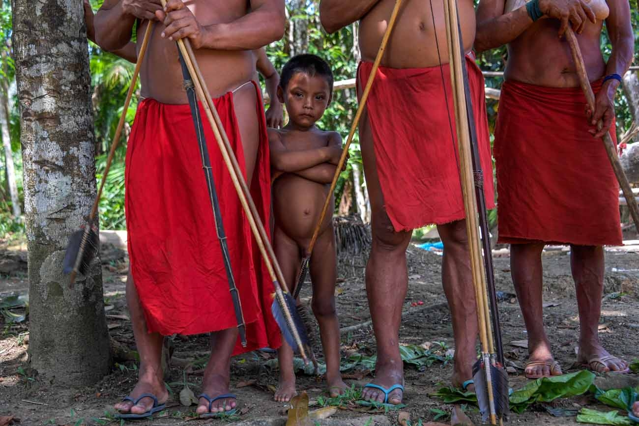 A Waiapi boy stands behind adults at the Pinoty village in Waiapi indigenous reserve in Amapa state in Brazil on October 12, 2017.  Tribal chieftain Tzako Waiapi perfectly remembers the day almost half a century ago when his hunting party stumbled across