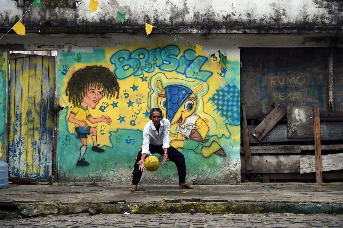 A Brazilian man plays football in Porto Seguro on June 28, 2014, during the Brazil-hosted 2014 FIFA World Cup.