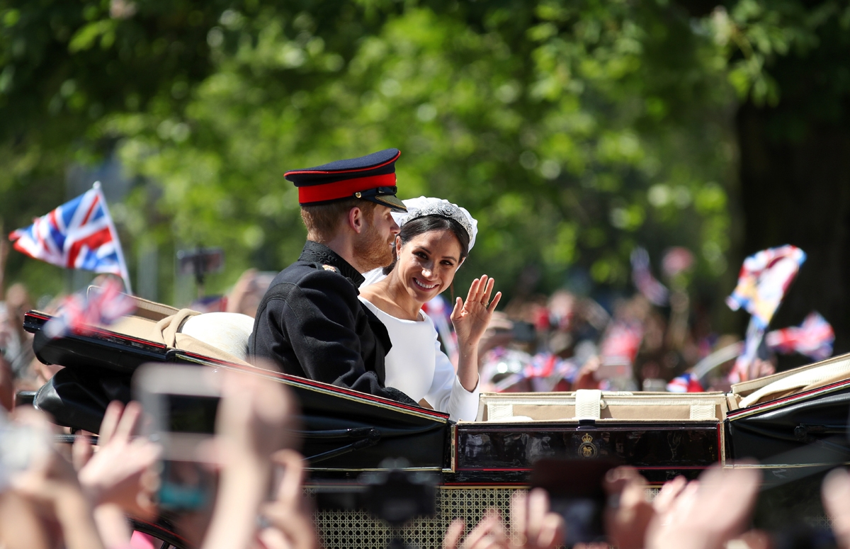 Britain's Prince Harry, Duke of Sussex and his wife Meghan, Duchess of Sussex wave from the Ascot Landau Carriage during their carriage procession on the Long Walk as they head back towards Windsor Castle in Windsor, on May 19, 2018 after their wedding ce