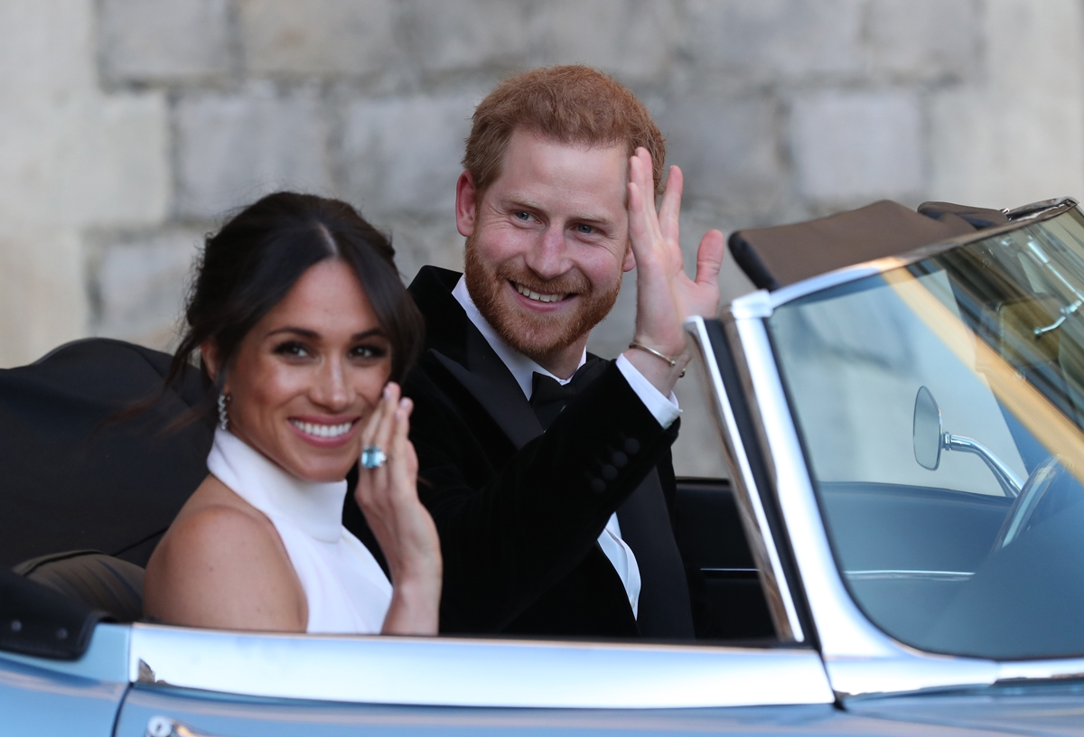 Britain's Prince Harry, Duke of Sussex, (R) and Meghan Markle, Duchess of Sussex, (L) leave Windsor Castle in Windsor on May 19, 2018 in an E-Type Jaguar after their wedding to attend an evening reception at Frogmore House.