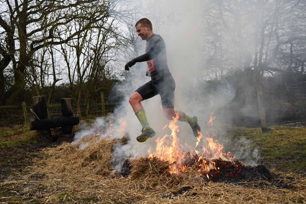 A competitor jumps a burning bale of hay as he takes part in the 'Tough Guy' adventure race near Wolverhampton, central England, on January 29, 2017.  The Tough Guy event, which is being held for the final time in its 30th year, challenges thousands of co