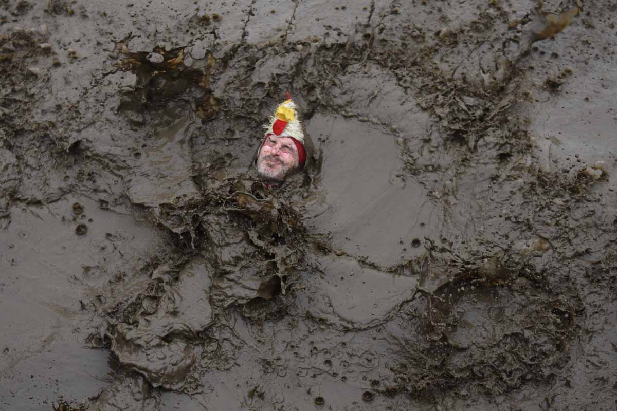 A competitor goes into a muddy pool as he takes part in the 'Tough Guy' adventure race near Wolverhampton, central England, on January 29, 2017.  The Tough Guy event, which is being held for the final time in its 30th year, challenges thousands of competi