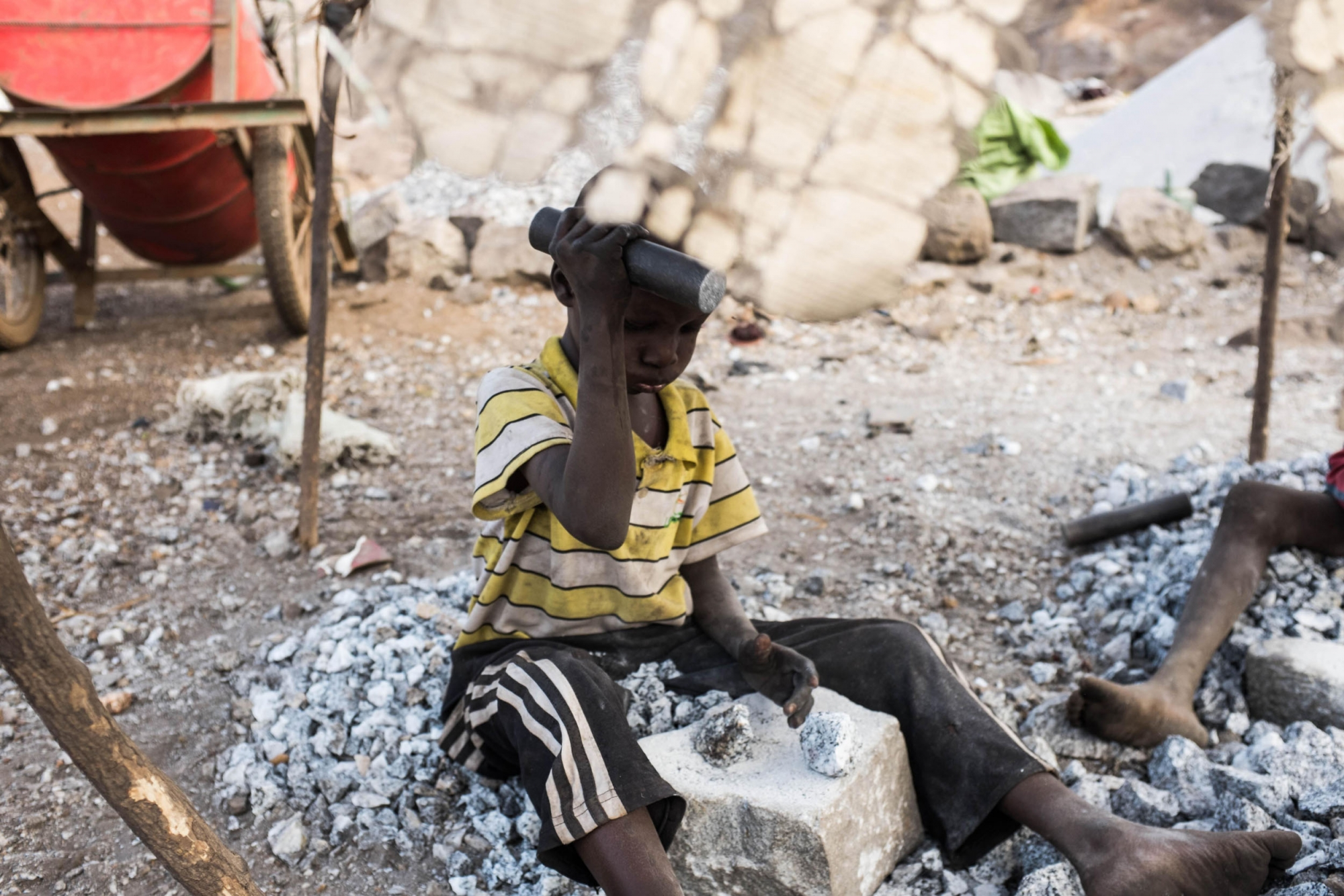A young boy crushes stones at a quarry in Ouagadougou where adults and children work on December 21, 2015.