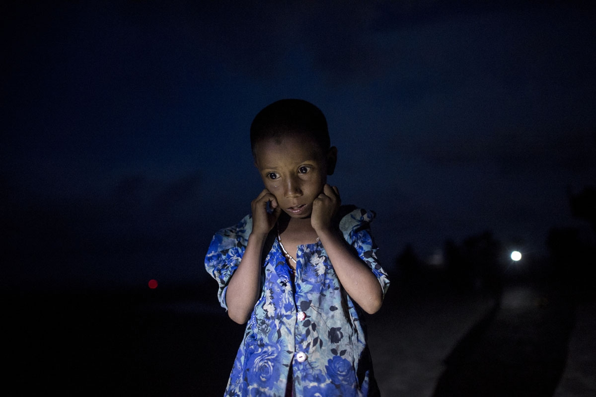 A Rohingya Muslim refugee walks by night after crossing the border from Myanmar, on the Bangladeshi shores of the Naf river in Teknaf on September 29, 2017.