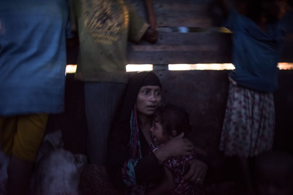 A Rohingya Muslim refugee holds her daughter as they are evacuated in a truck to a refugee camps after crossing the Naf River, in Teknaf, Bangladesh's Ukhia district on October 8, 2017.