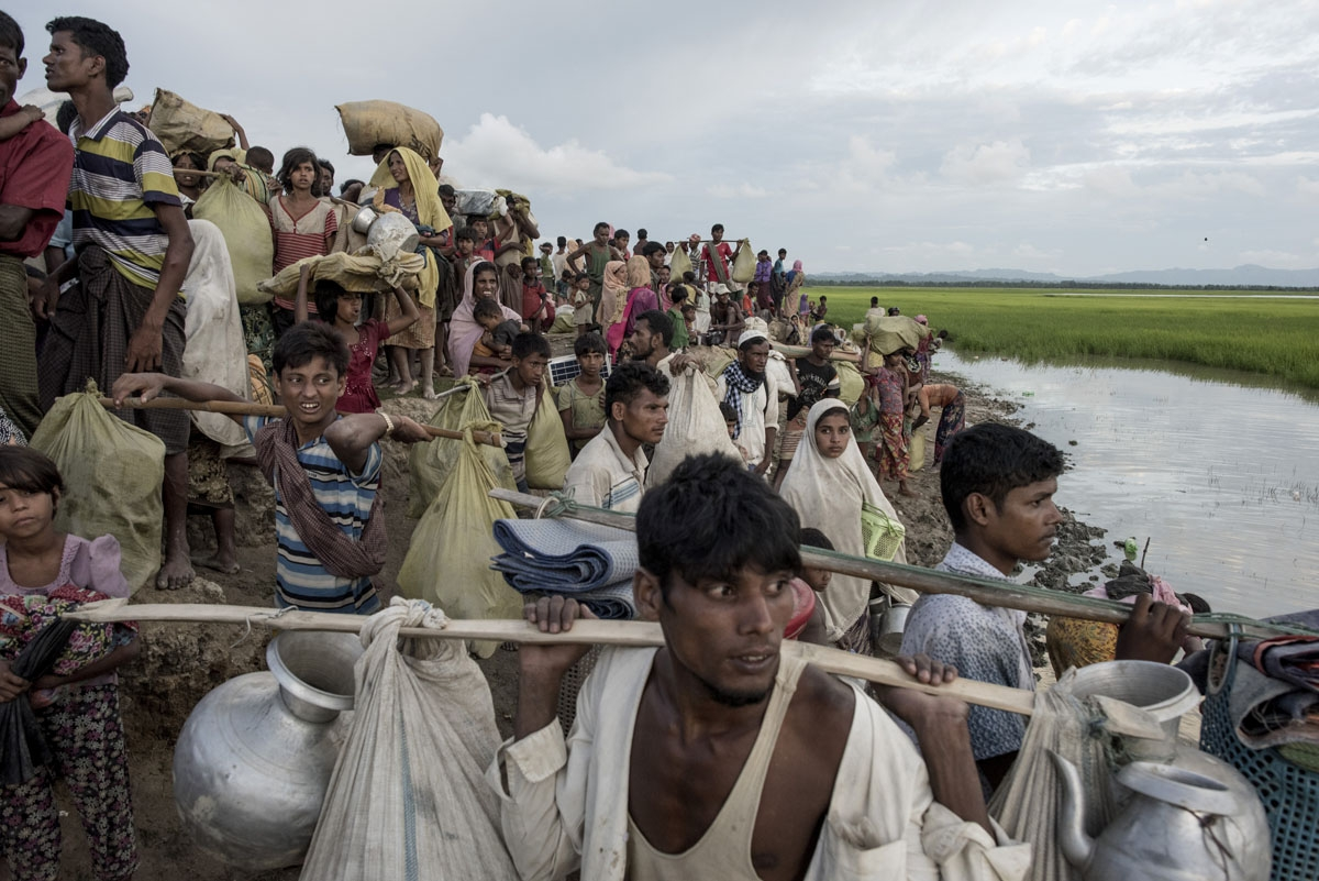 Rohingya refugees walk with their belongings after crossing the Naf river from Myanmar into Bangladesh in Whaikhyang on October 9, 2017.