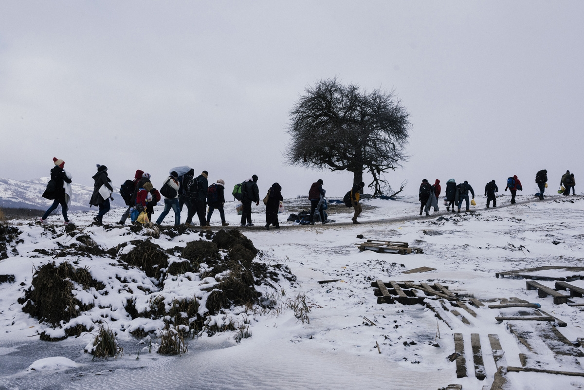 Migrants and refugees walk through snow covered fields, after crossing the Macedonian border into Serbia near the village of Miratovac, on January 18, 2016.     More than one million migrants reached Europe in 2015, most of them refugees fleeing war and v