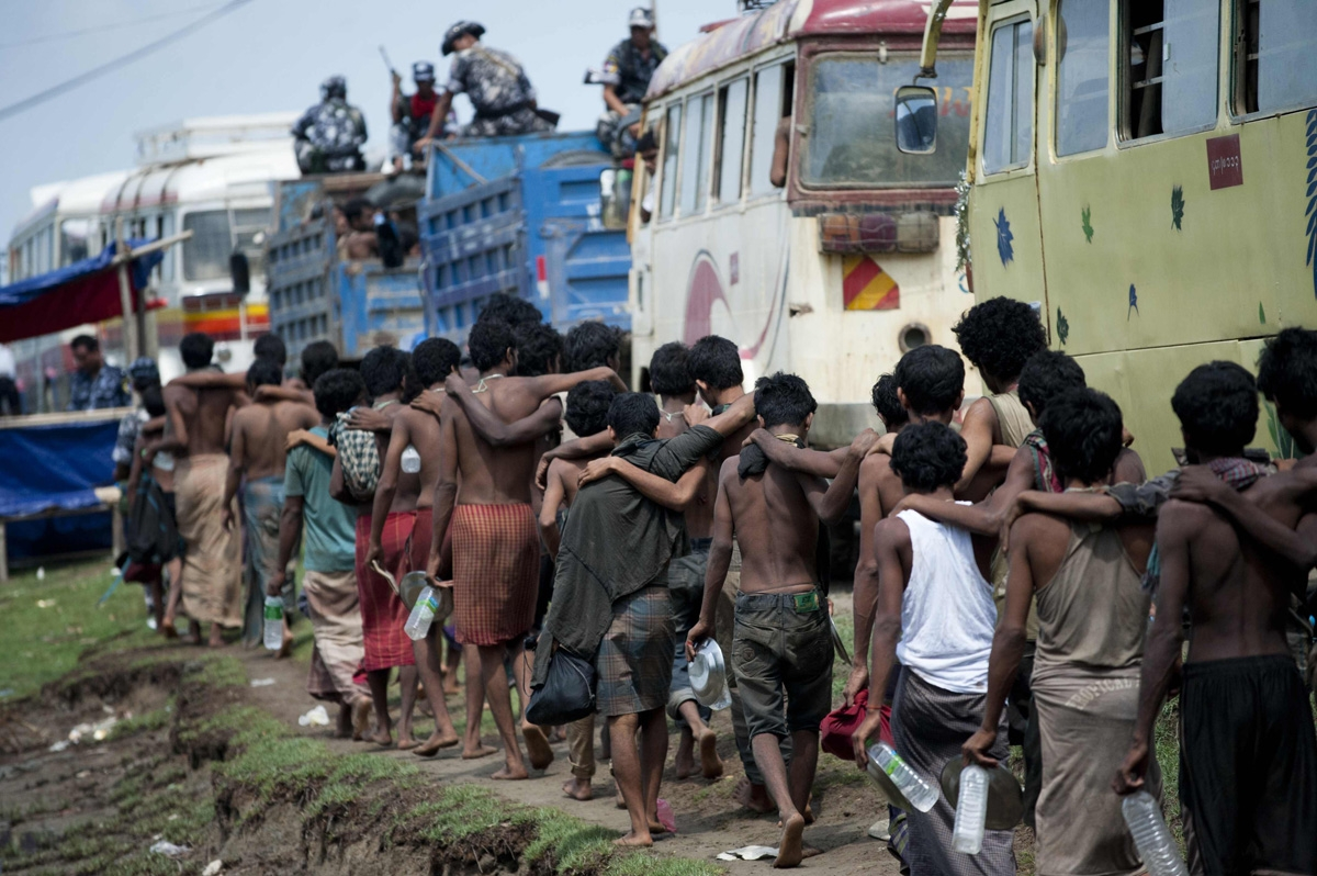 Migrants, who were found at sea on a boat, leave as they are moved from a temporary shelter near the Kanyin Chaung jetty to MeeThike sub-township outside Maungdaw township, northern Rakhine state on June 4, 2015.  More than 700 migrants found adrift on a