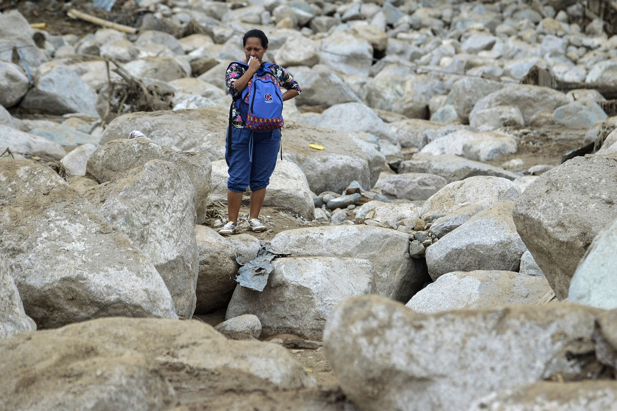 A woman cries amidst the rubble left by mudslides following heavy rains in Mocoa, Putumayo department, southern Colombia on April 2, 2017.