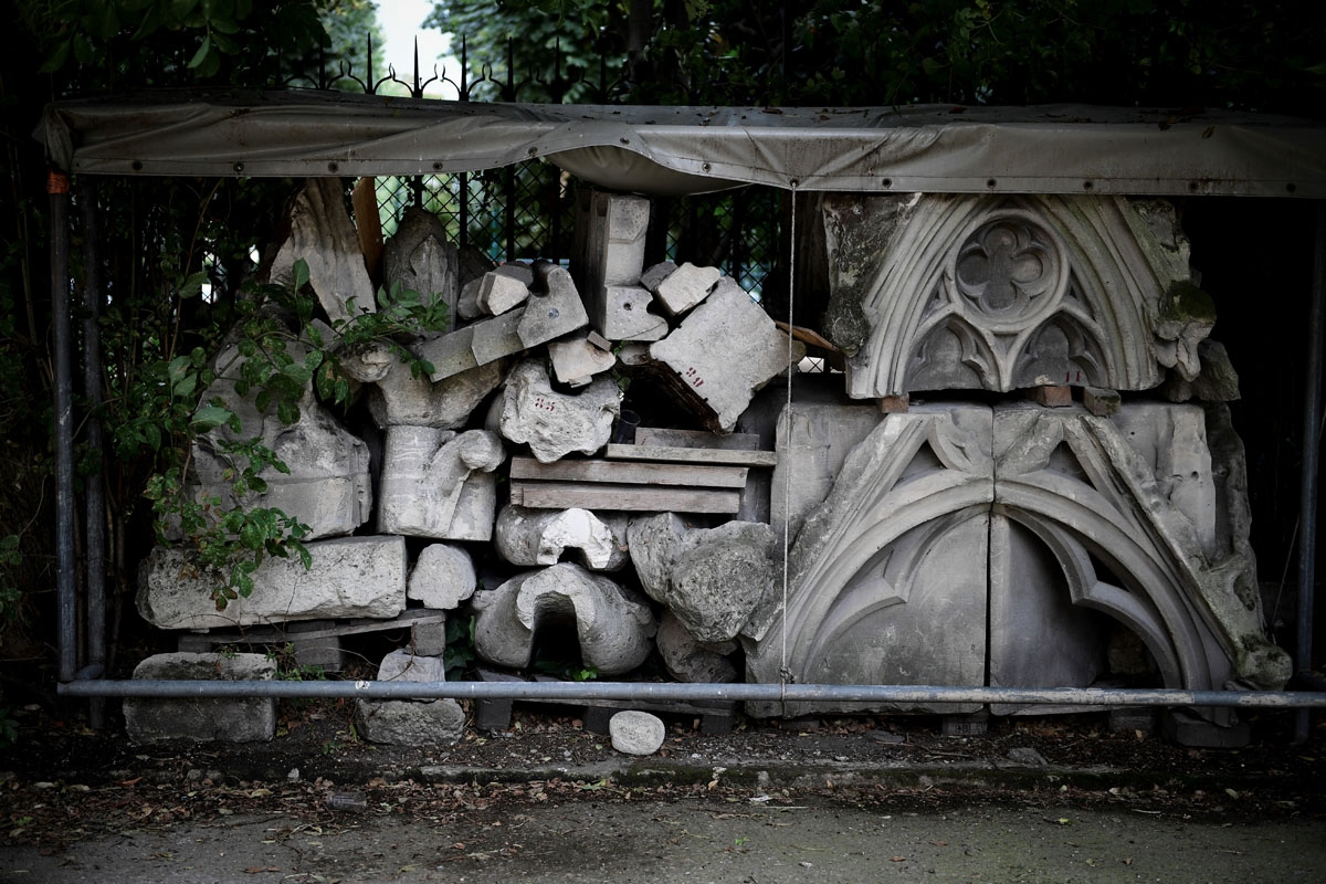 A picture taken on June 28, 2017 shows remains of Notre-Dame cathedral in Paris, stored in a garden, as the monument needs a huge restoration.