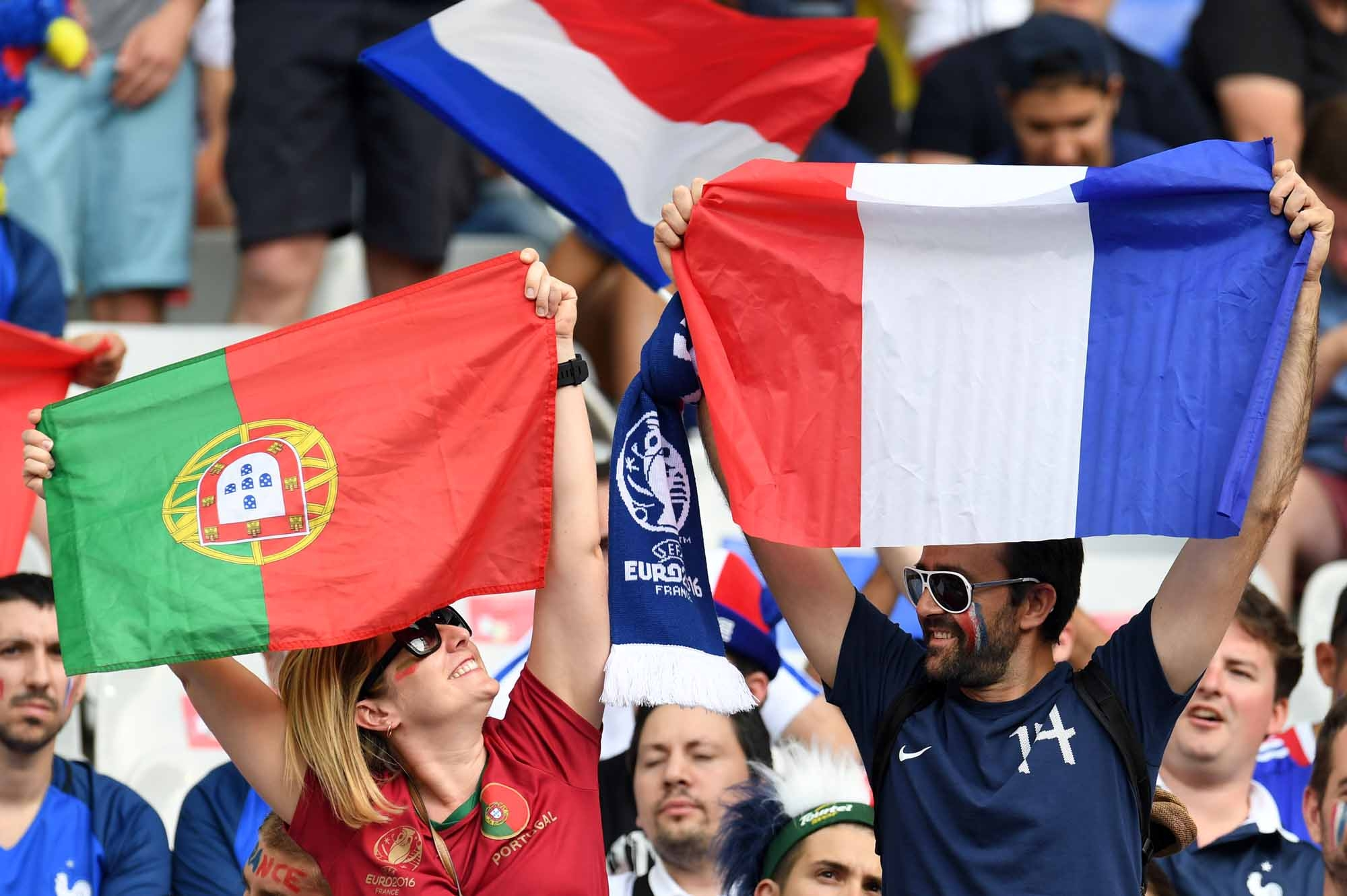 Supporters wave Portuguese and French flags ahead of the Euro 2016 final football match at the Stade de France in Saint-Denis, north of Paris, on July 10, 2016. / AFP PHOTO / PATRIK STOLLARZ
