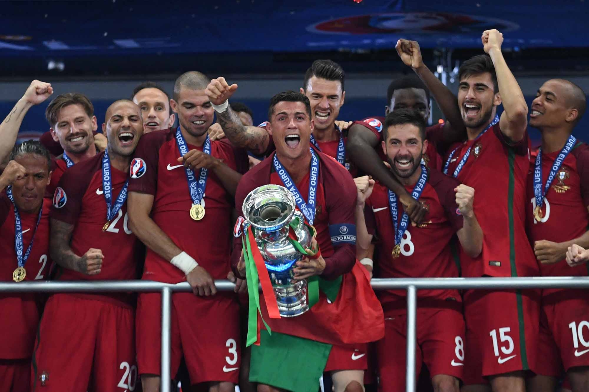 Portugal's forward Cristiano Ronaldo (C) lifts the trophy as he celebrates with teammates winning the Euro 2016 final football match between Portugal and France at the Stade de France in Saint-Denis, north of Paris, on July 10, 2016. / AFP PHOTO / FRANCIS