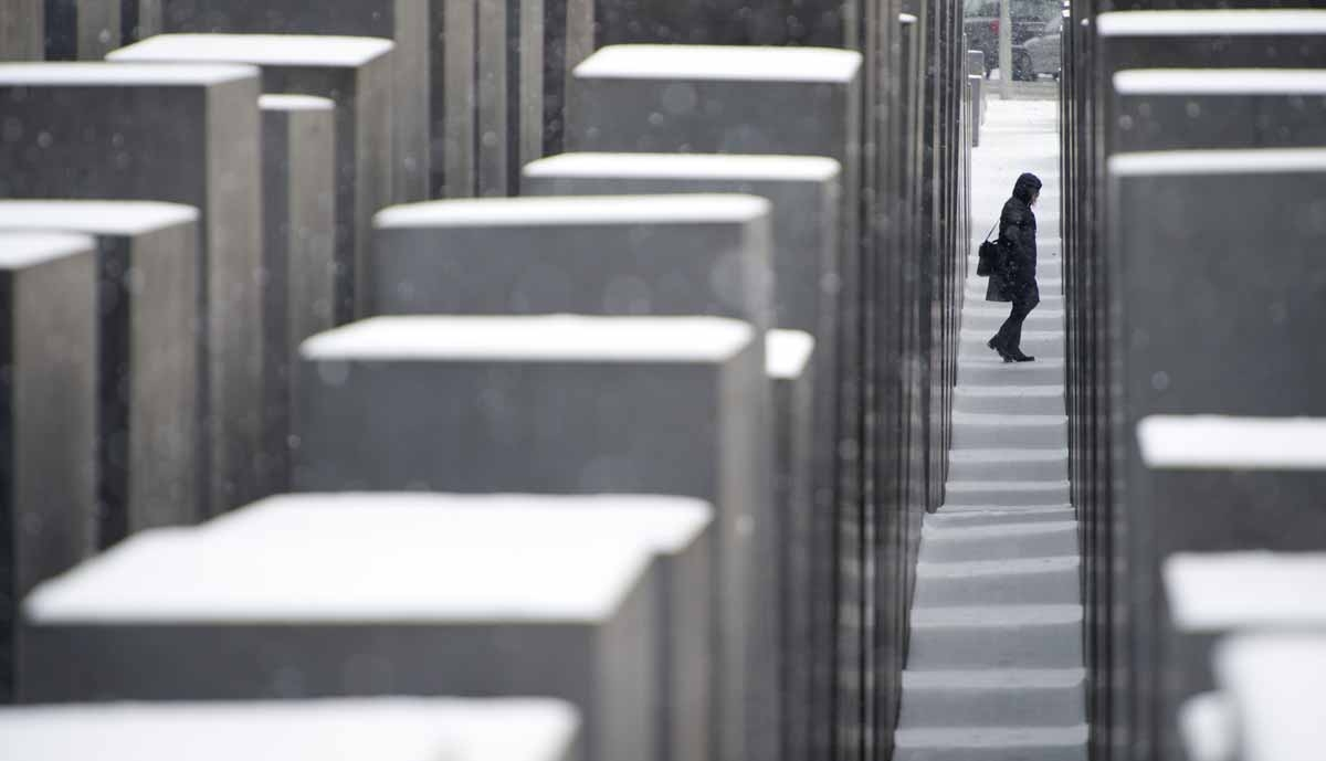A visitor walks among the snow covered concrete slabs at the Memorial for the murdered Jews in Europe in Berlin on January 14, 2013. Temperature dropped over night and snow followed at daybreak in the German capital.