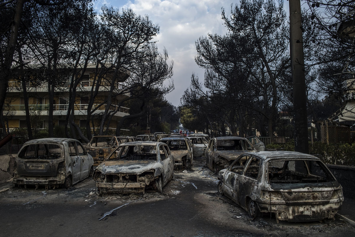 This photo taken on July 24, 2018 show cars burnt following a wildfire at the village of Mati, near Athens, on July 24, 2018.
