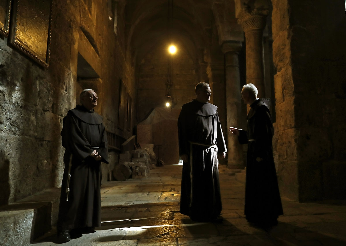 Franciscan friars discuss in a corridor in the Church of the Holy Sepulchre in the Old City of Jerusalem, on February 21, 2018. Dispatched to the city 800 years ago by the Catholic order's founder, Saint Francis of Assisi, the Franciscans have for centuri