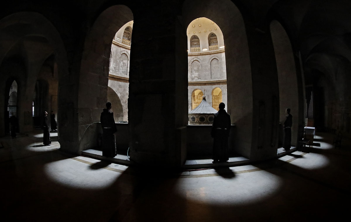 Franciscan friars observe the tomb of Jesus from the gallery at the Church of the Holy Sepulchre in the Old City of Jerusalem, on February 17, 2018.  Dispatched to the city 800 years ago by the Catholic order's founder, Saint Francis of Assisi, the Franci