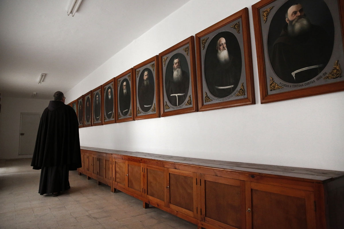 A Franciscan friar walks past the portraits of former Custos placed in a dedicated room at the St Saviour Monastery, the Franciscan headquarters in the Old City of Jerusalem, on January 25, 2018.