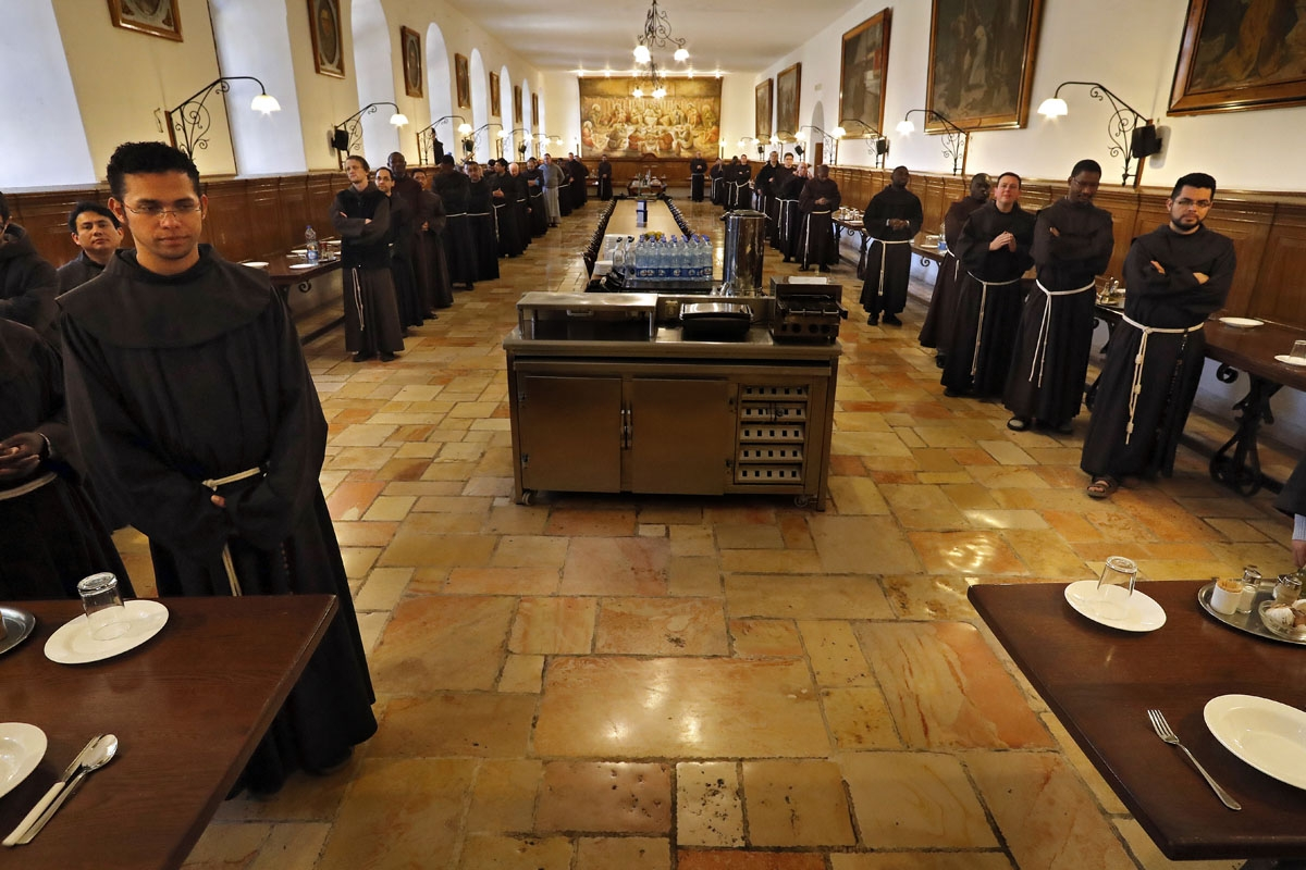 Franciscan friars pray before having dinner at the refectory inside the Saint Saviour Convent, the Franciscan headquarters in the Old City of Jerusalem, on March 15, 2018.
