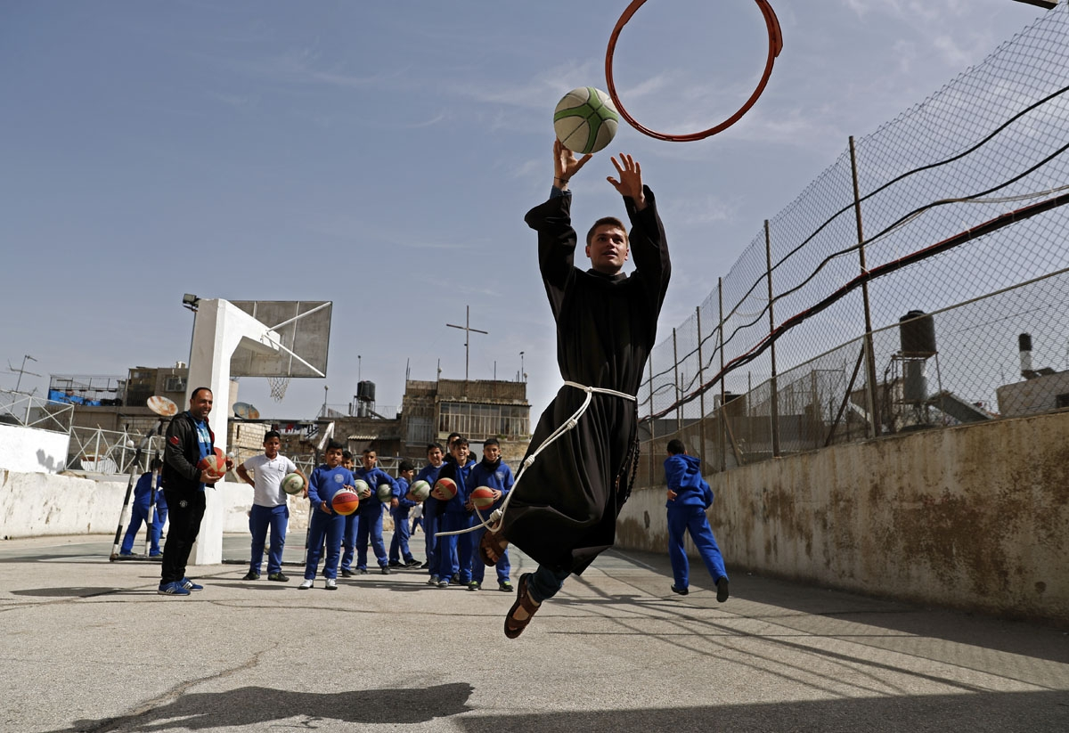 A Franciscan friar plays basketball with Palestinian children from the Terra Sancta school during a sport session in the Old City of Jerusalem, on March 1, 2018.