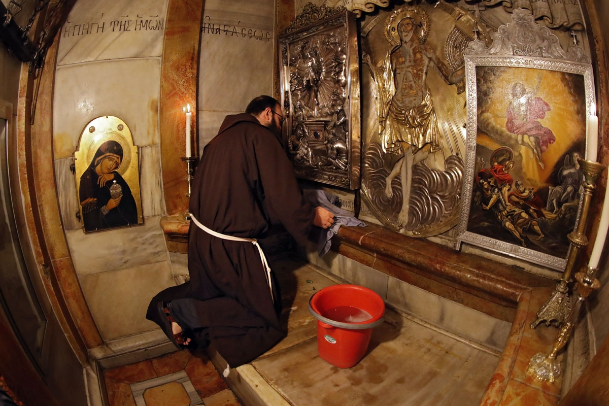 Croatian friar Sinisa Srebrerovic cleans the ornaments inside a tomb believed to the burial site of Jesus Christ on March 2, 2018.