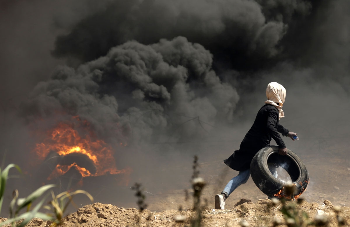 A Palestinian girl carries a tire in flames during clashes with Israeli security forces near the Israeli border fence, east of Gaza City in the central Gaza Strip on April 13, 2018. - Several thousand Gazans gathered for a third consecutive Friday of mass