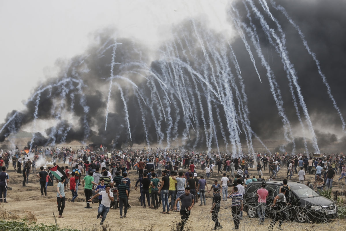 Palestinian protesters flee from incoming teargas canisters during clashes with Israeli forces along the border with the Gaza strip east of Gaza City on May 4, 2018, on the sixth straight Friday of mass demonstrations calling for the right to return to th