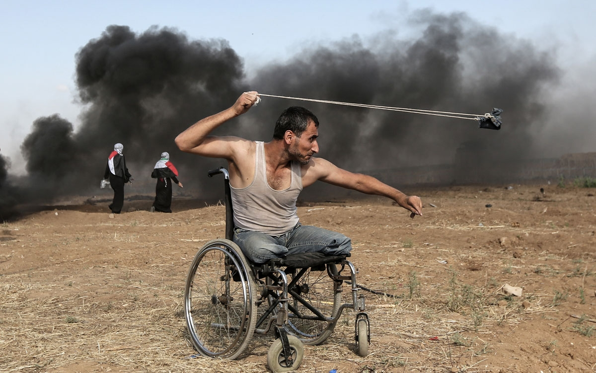 Palestinian Saber al-Ashkar, 29, hurls rocks during clashes with Israeli forces along the border with the Gaza strip, east of Gaza City, on May 11, 2018, as Palestinians demonstrate for the right to return to their historic homeland in what is now Israel.