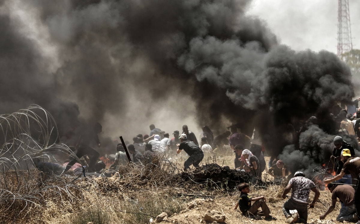 Palestinians clash with with Israeli forces near the border between the Gaza strip and Israel east of Gaza City on May 14, 2018, as Palestinians protest over the inauguration of the US embassy following its controversial move to Jerusalem.