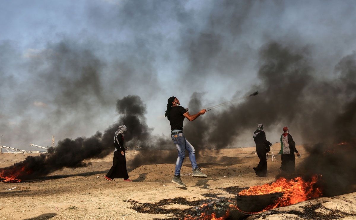 A Palestinian man uses a slingshot to throw a stone towards Israeli forces as smoke billows from burning tyres during a demonstration along the border with the Gaza strip east of Gaza city on June 1, 2018.