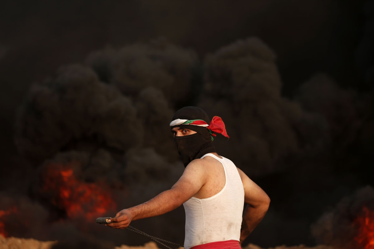 A masked palestinian protester stands by smoke rising from burning tyres during a protest near the border with Israel east of Gaza City on August 31, 2018.