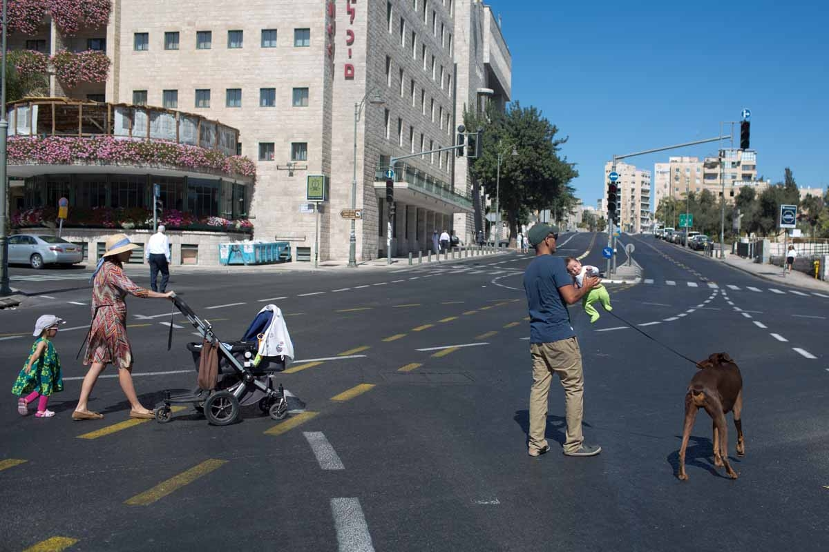 An Israeli family walks on a car-free road in Jerusalem during the solemn Jewish fast of Yom Kippur on October 4, 2014. Yom Kippur, which means the Day of Atonement, is marked with a 25-hour fast beginning before sunset the previous day.