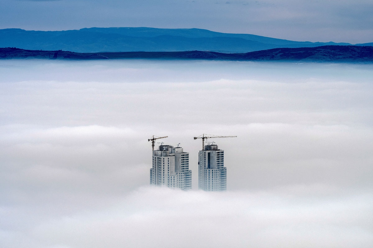 A picture taken from Vodno Mountain shows the tops of some of the city's highest buildings above clouds in an area with a high level of air pollution in Skopje on December 15, 2017.