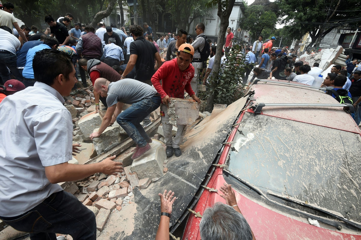 People remove debris of a building which collapsed after a quake rattled Mexico City on September 19, 2017.