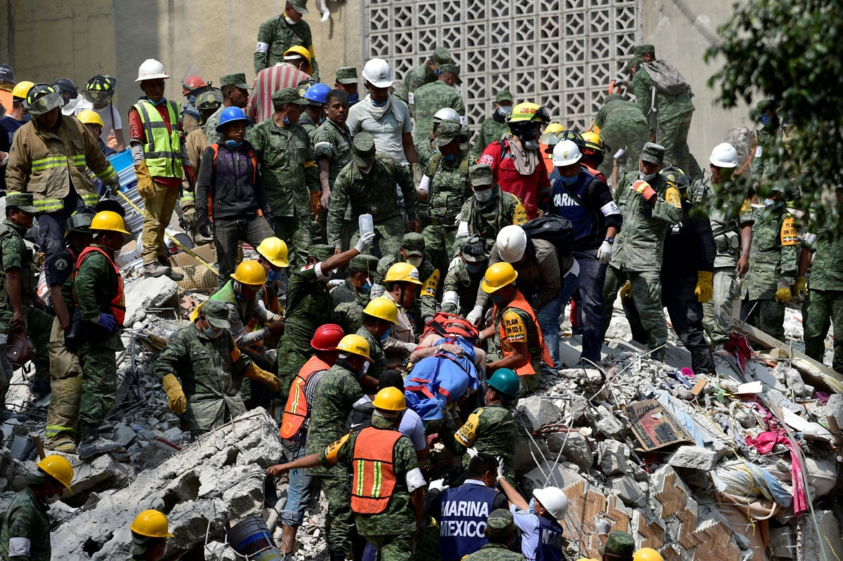 A man is pulled out of the rubble alive in Mexico City on September 20, 2017 as the search for survivors continues a day after a strong quake hit central Mexico.