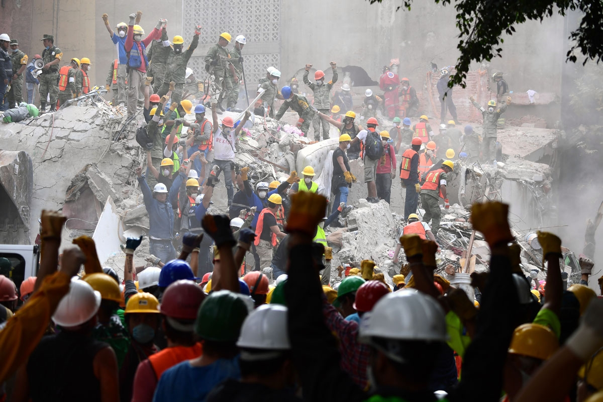 Rescuers make the signal for silence during the search for survivors in a flattened building in Mexico City on September 21, 2017, two days after a strong quake hit central Mexico killing at least 240 people.