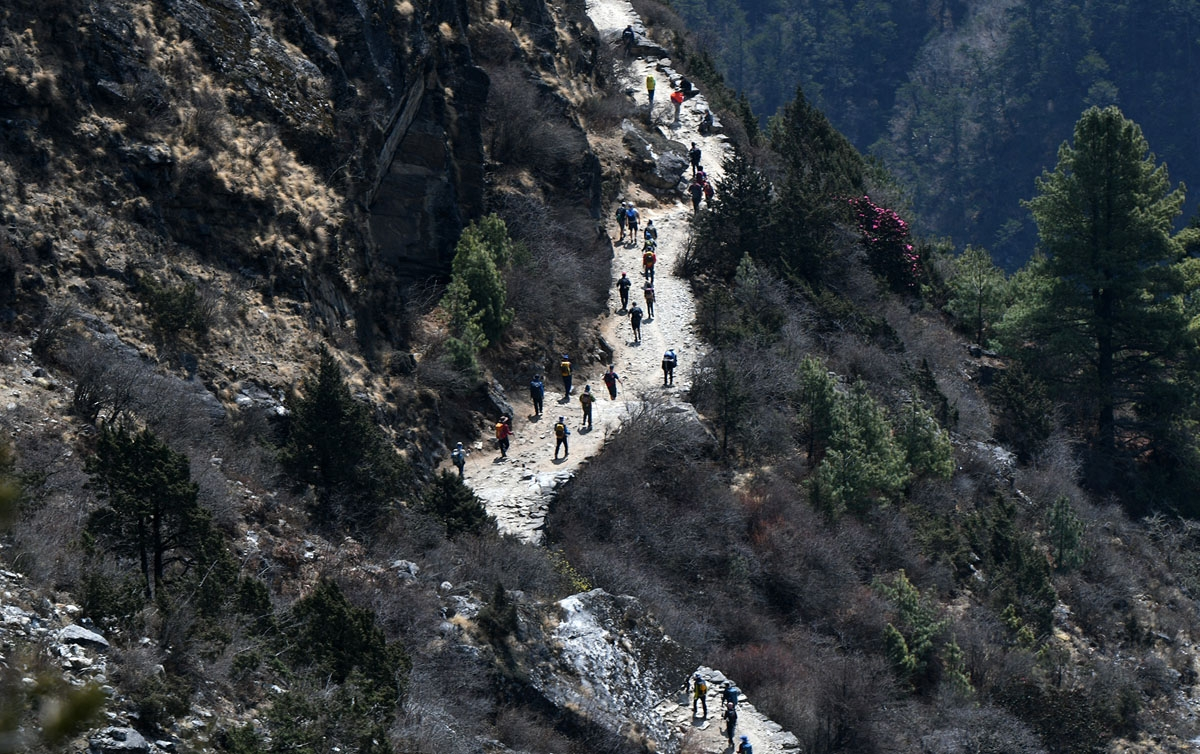 Trekkers and porters walk along a path in the Everest region, April 17, 2018.