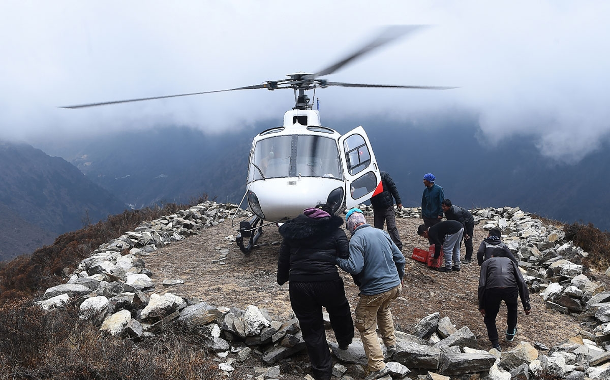 An unidentified injured person is helped to board a helicopter at the Mong La village near Namche Bazar, April 17, 2018.