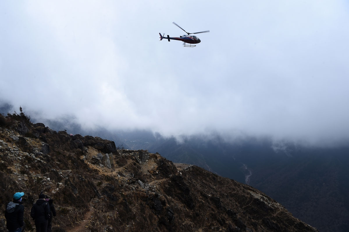 A helicopter comes in to land at Mong La village near Namche Bazar, April 17, 2018.