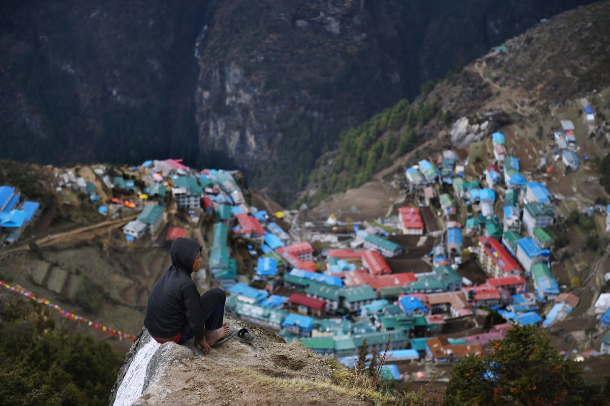 Nepali porter Milan Rai, 14, rests as he makes his way up a rocky path high above the north-eastern town of Namche Bazar, April 18, 2015.