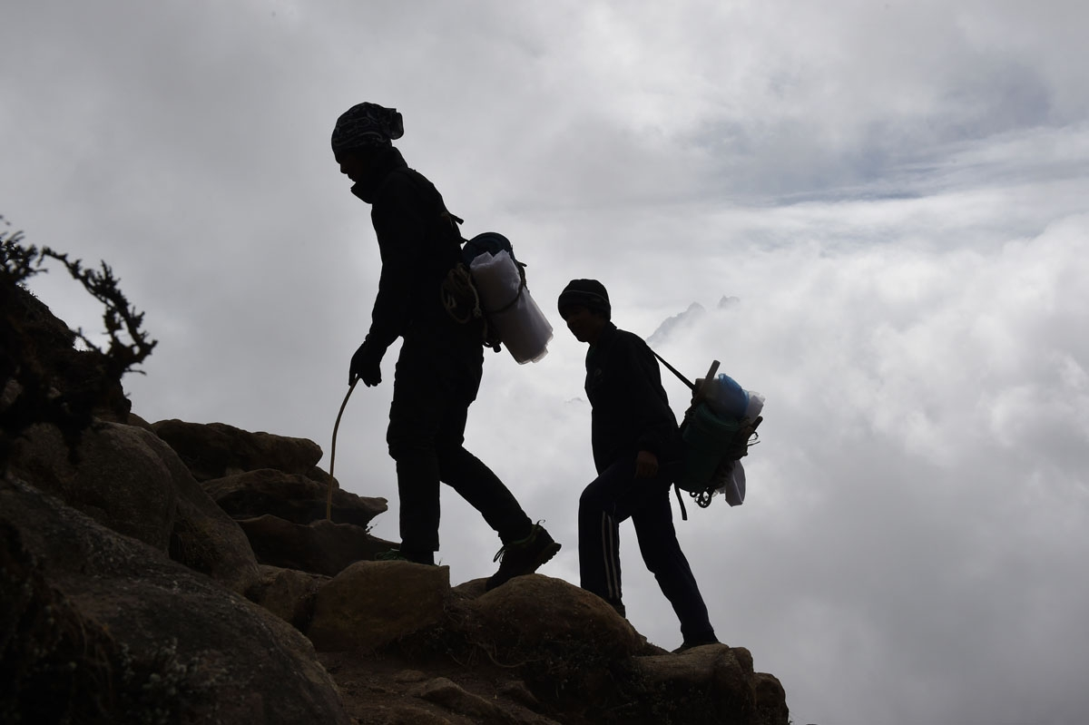 Nepalese porters walk up a path high above the north-eastern town of Namche Bazar, April 18, 2015.